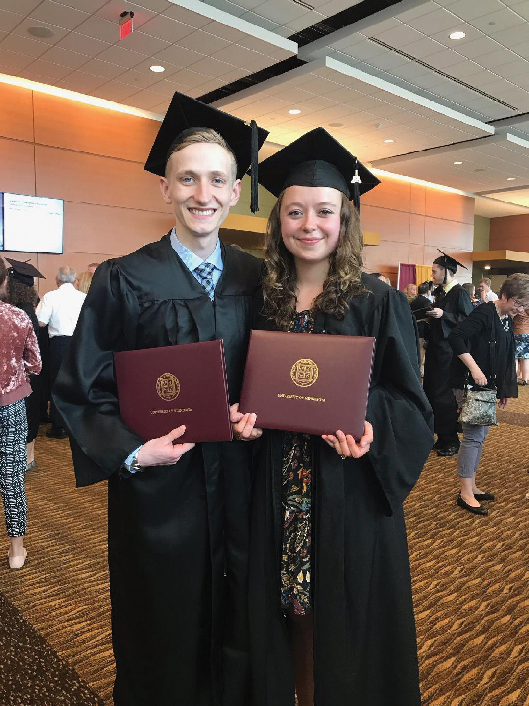 University of Minnesota alums Brady and Cassie Zell smile in commencement robes while holding their diplomas