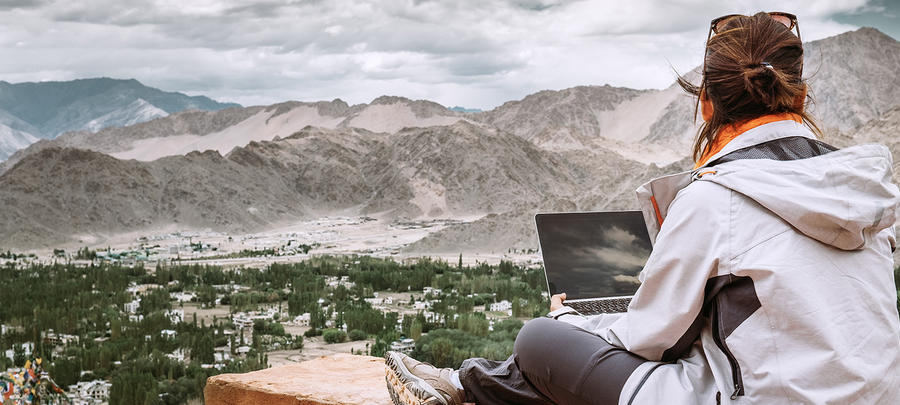 Traveler with laptop sits on top view point on the mountain valley